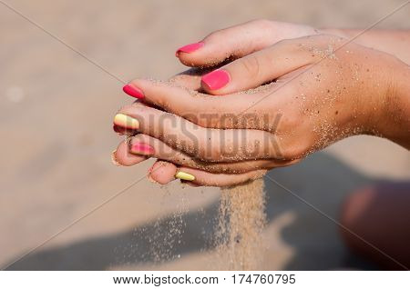 Girl sifting sand through her fingers. Hands close-up