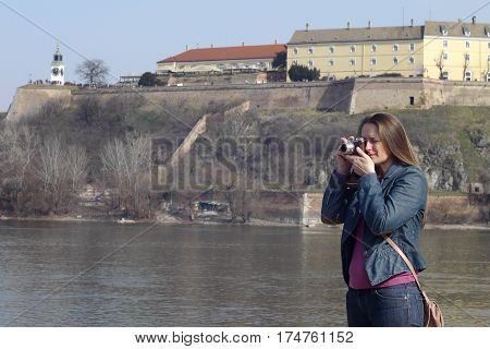 Young woman with vintage retro film camera takes photos on the bank of  the Danube river and Petrovaradin fortress near Novi Sad in Serbia.