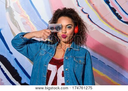 Delighted young lady with flashy makeup hearing song through headset while having fun with audiotape. Retro style concept