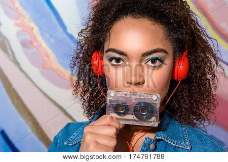 Portrait of Calm african female with strident colour look listening music through earphones while holding audiocassette in arm