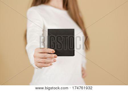 Girl Showing Blank Black Square Flyer Brochure Booklet. Leaflet Presentation. Pamphlet Hold Hands. W