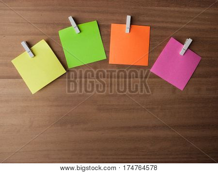 Four Post It notes displayed in an arc on small pegs layed out on softly grained wood