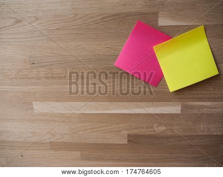 A pair of Post Its on a lightly grained wooden background.