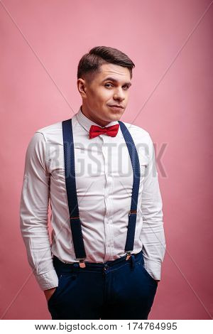 young cheerful stylishly dressed man suspiciously eyeing on a pink background