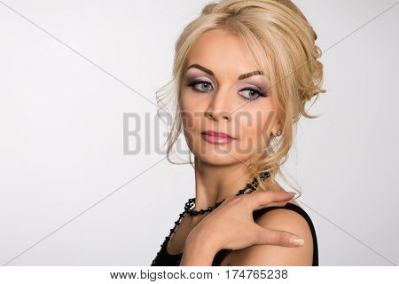 Charming blonde with a fashionable hairstyle on a gray background