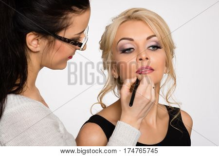 Visagiste doing make-up of a beautiful young girl in the studio