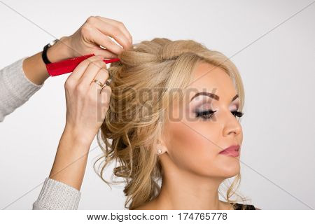 Hairdresser makes hair styling blond girl in a beauty salon