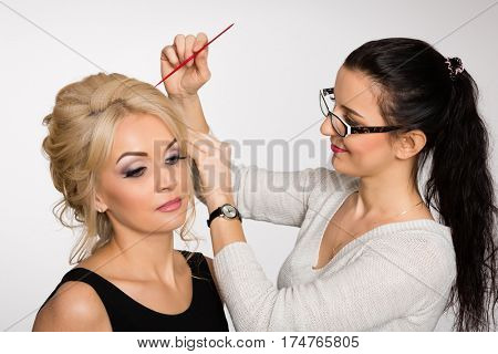 Stylist-hairdresser makes hair styling blond girl in a beauty salon