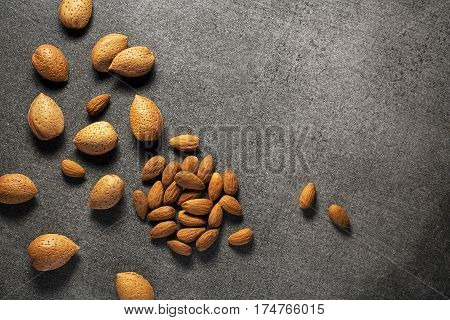 Almonds in their skins and peeled on gray background