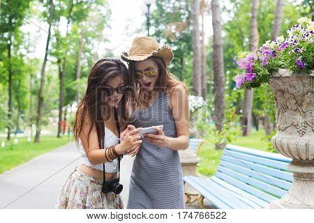 Two girls friends outdoors surprised watching photos at mobile phone. Young female tourists having fun in summer park. Travelling together, lifestyle portrait.