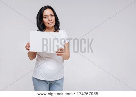Asking for attention. Confident attractive contemporary lady posing for a photographer while standing isolated on white background and holding up a sign