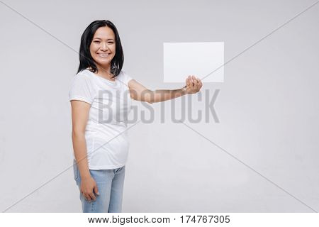 Write something here. Inspiring lovely fabulous lady holding a sign in her hand while standing isolated on white background and wearing no make up