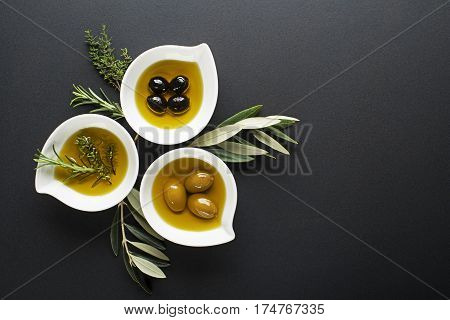 Olive oil with fresh herbs on black background.