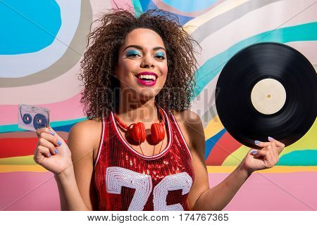 Portrait of Happy woman with headset on neck holding audiocassette and music platter while situating near painting wall