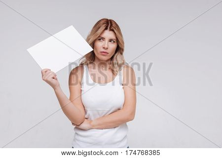 Concerning thoughts. Open minded nice contemporary woman wondering about something while holding a piece of paper and participating in all white things photoshoot