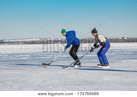DNEPR UKRAINE - JANUARY 22, 2017: Amateur men playing hockey on a frozen river Dnepr in Dnepr city, Ukraine at January 22, 2017