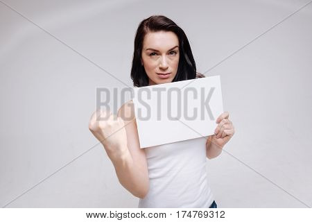 We can do it. Positive classy modern woman standing isolated on white background and holding up her fist while posing for a photographer