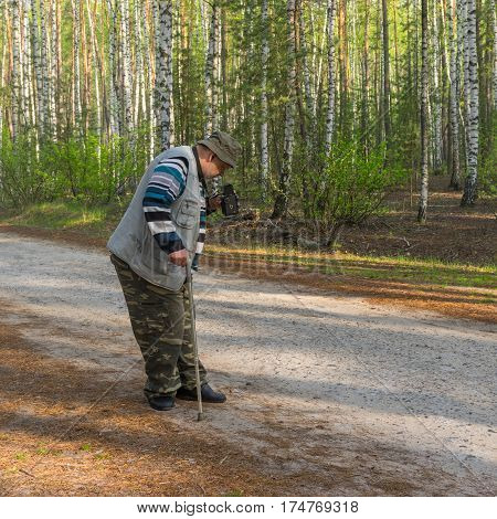 Old photographer making photo with old film camera in morning birch forest