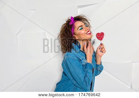 Happy young woman with bright look holding candy in form of heart. Copy space