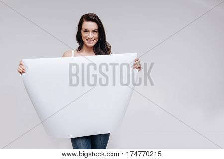 Pay some attention. Energetic elegant young woman posing for a professional photographer while working on a campaign and showing a big blank sheet of paper
