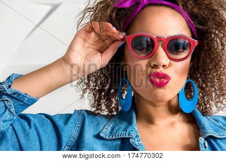 Outgoing young woman with bright look and with different accessories sending kiss with passion