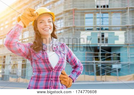 Portrait of Young Female Construction Worker Wearing Gloves, Hard Hat and Protective Goggles at Construction Site.
