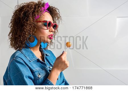 Serene young woman wearing sunglasses and watching at lollipop while holding it in arm. Copy space