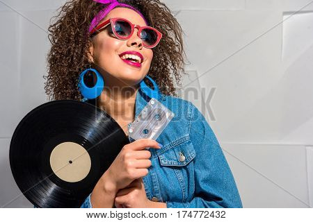 Happy african female with various accessories holding phonograph record and audiotape