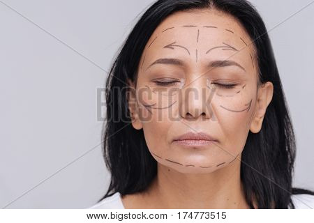 Not perfect. Serious dreamy young mature lady posing for a photographer with lines drawn upon her face and standing isolated on white background