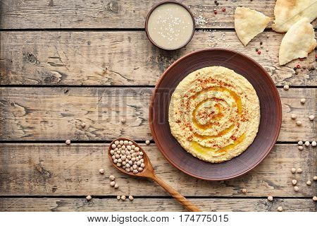 Hummus traditional snack chickpea vegan natural nutrition lunch dip paste with pita bread paprika tahini and olive oil in clay plate on rustic flat lay. Healthy dietary fiber protein food