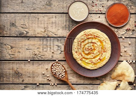 Hummus traditional homemade eastern snack chickpea vegan natural nutrition lunch dip paste with paprika tahini and olive oil in clay plate on rustic flat lay. Healthy dietary fiber protein food