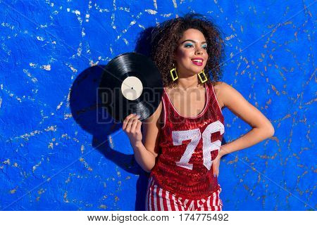 Happy african female with curly hairs swishing by music platter while standing near wall