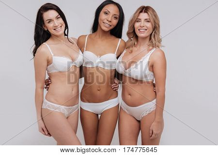 Open minded female community. Positive confident inspirational women standing close to each other while wearing lingerie and promoting natural beauty