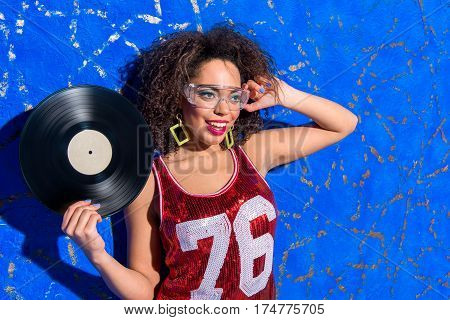 Portrait of Outgoing deejay holding gramophone record and wearing glasses while locating against blue background