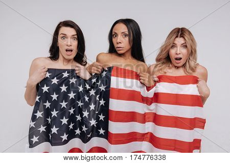 What are you looking at. Daring expressive lovely ladies using a flag covering their bodies while posing for a professional photographer in a studio