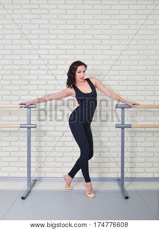 Beautiful woman dancer posing near barre in ballet studio