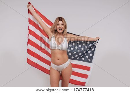 Free to do anything. Confident radiant joyful woman posing with a national flag wearing only her underwear and standing isolated on white background
