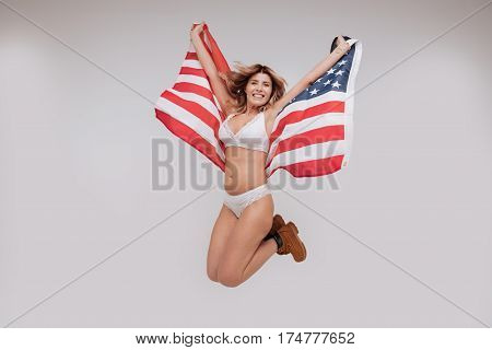 Like a butterfly. Lively energetic emotional woman having a fun photoshoot while wearing her underwear and using a flag as accessory