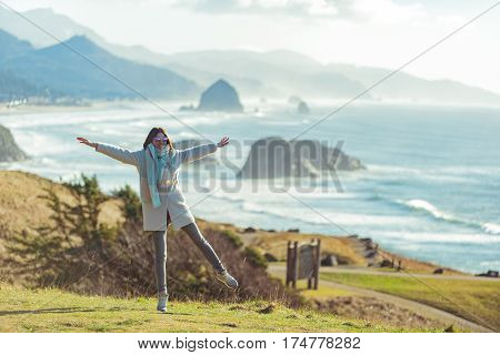 Outgoing young woman situating on shore near blue ocean opposite mountains