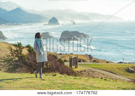 Pensive woman watching at ocean while locating on seashore in Oregon