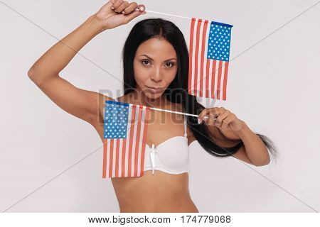 Waving flags. Confident artistic active lady accentuating her origin and representing a proud citizen while working on national beauty campaign