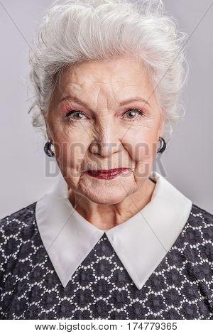 Enjoying good long life. Waist up portrait of smiling senior female posing isolated gray background
