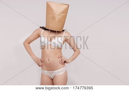 Body is just a shell. Sensual confident hypnotic woman posing in her underwear while standing isolated on white background and hiding her face