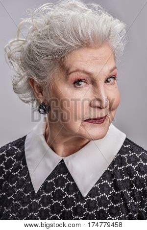 Confidence comes with age. Portrait of cheerful elderly lady standing isolated on gray background and smiling playfully