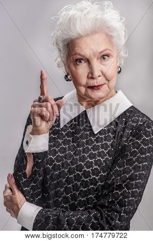 Positive outlook throughout years. Portrait of senior stylish female standing in studio and holding her index finger at top, isolated on gray background