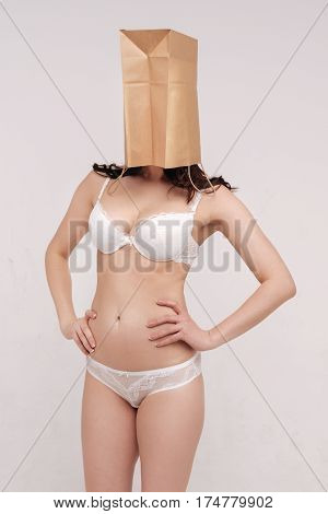 Judging by the cover. Young dedicated female activist showing off her body and hiding her face under paper bag while working on natural beauty campaign