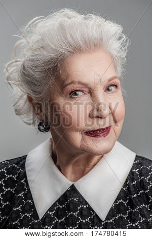 Poised and positive. Portrait of senior woman looking relaxed and happy isolated on gray background