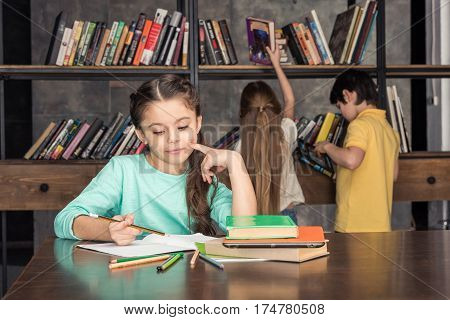 portrait of pensive girl doing homework with classmates looking for books behind