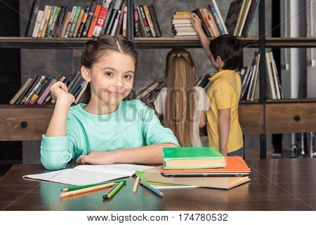 portrait of smiling girl sitting at table with classmates looking for books behind
