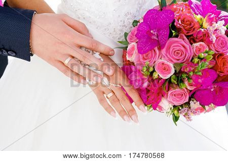 Hands with wedding rings on the background of white bridesmaid dresses and wedding bouquet of roses and orchids